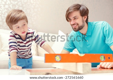 Straight and flat. Small boy applying a level playing with a wooden building kit with his father - stock photo