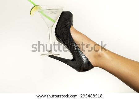 Straight bare sexy female leg in black leather shoe on high heel and cocktail with lime in glass on white background, horizontal picture - stock photo
