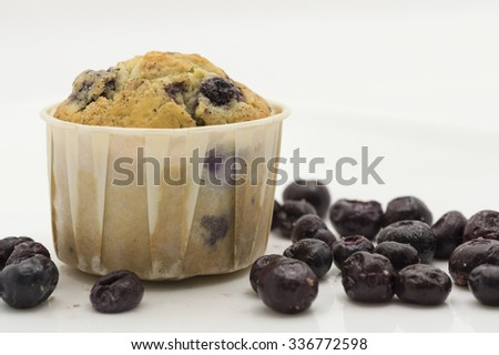 Straight closeup view of freshly baked blueberry muffin in souffle cup surrounded by fresh berries.  White background. - stock photo