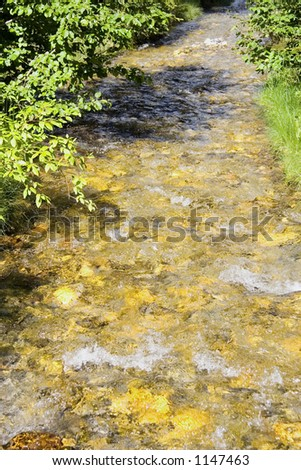 straight creek in the mountains - with sparkling water - stock photo
