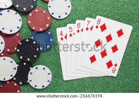 Straight Flush. Playing cards isolated on a green background with poker chips scattered  - stock photo