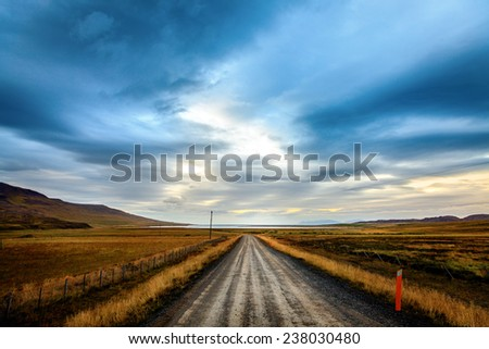 Straight gravel road through the fields in Northwestern Iceland - stock photo