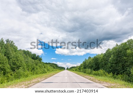 Straight highway surrounded by green forest recedes into the distance under cloudscape blue sky.   - stock photo