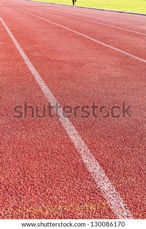 straight lanes of red cinder running track