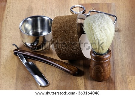 straight razor with accessories on wooden background