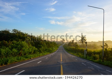 straight road and colorful sunset in thailand - stock photo