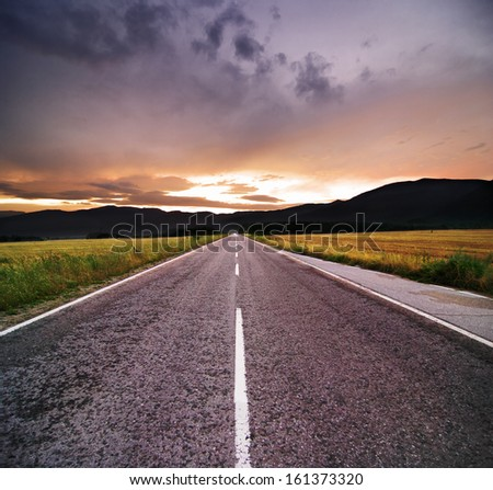 straight road at the sunset - stock photo