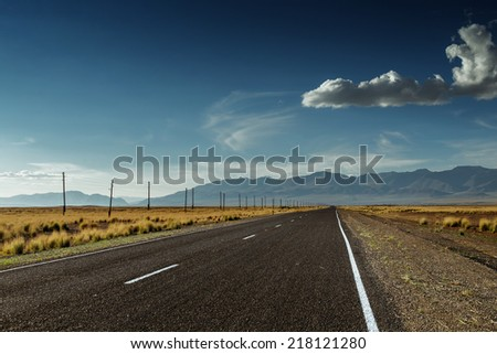 Straight road goes to horizon on background of mountains - stock photo