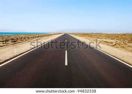 Straight road in a desert seascape. Andalusia, Spain. - stock photo