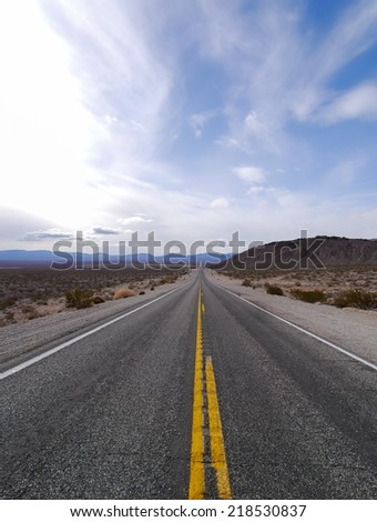 Straight road in desert landscape in Nevada, United States.
