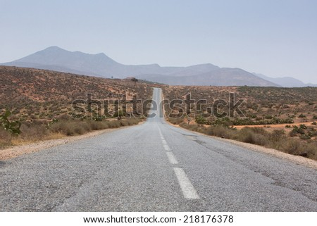 Straight road through the desert in the region of Tata, mountains in the background. Morocco, Africa - stock photo