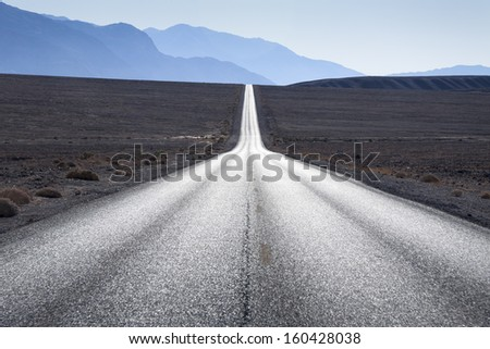 Straight road towards mountain range in horizon at Death Valley, USA - stock photo