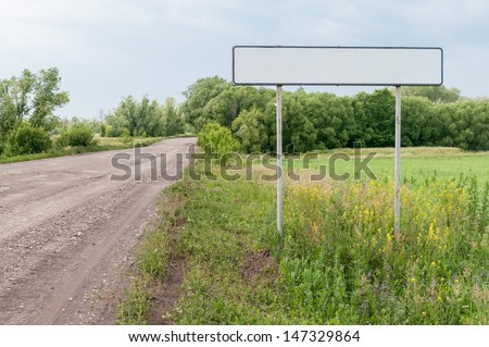 Straight road with white empty sign on roadside at the entrance to the city against beautiful summer landscape background. Bolshaya Doroga village, Tambovsky region, Russia.  - stock photo