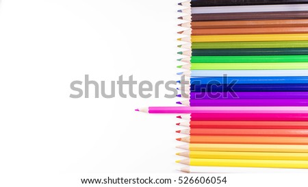 Straight row of multiple coloured pencils on white, with pink sticking out and space for text