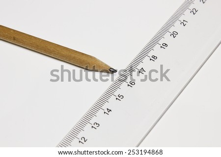 Straight ruler and a pencil on a white table background.