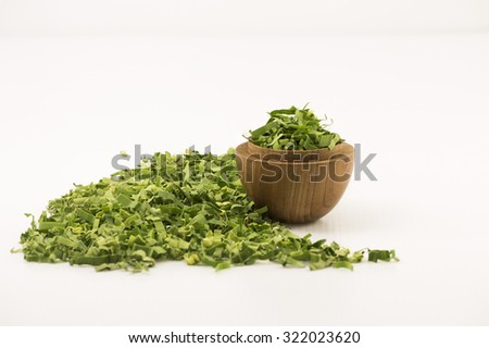 Straight view focus on shredded pandan leaf in a wooden bowl. Partially focus loose leaf by the side of the bowl with white background.  The sweet fragrance herbal tea leaf has medicinal benefits. - stock photo