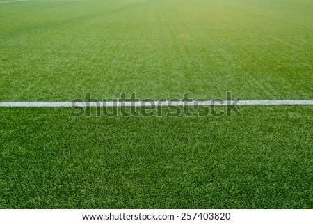 Straight white chalk line marking on grass background. - stock photo