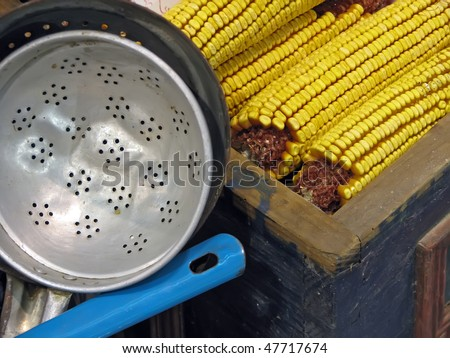 strainer and corn. vintage metal strainer and cob of corn.