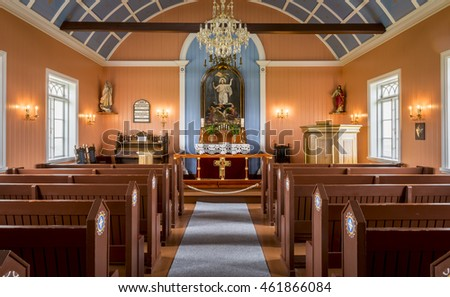 Strandakirkja, Iceland - June 25, 2016: Interior of the Strandakirkja church with red benches and blue painted ceiling with yellow stars in Iceland.