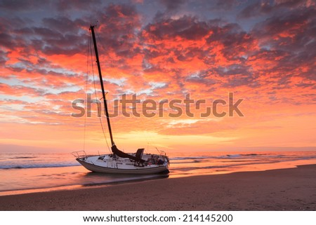 Stranded boat on the Cape Hatteras National Seashore in the Outer Banks of North Carolina at sunrise. - stock photo