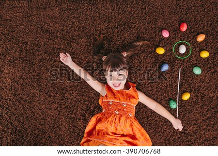 strange, funny, cheerful little girls with abstract flower. easter egg. top view. flat lay. happy kid. little child. orange dress. enjoyment .enjoy - stock photo