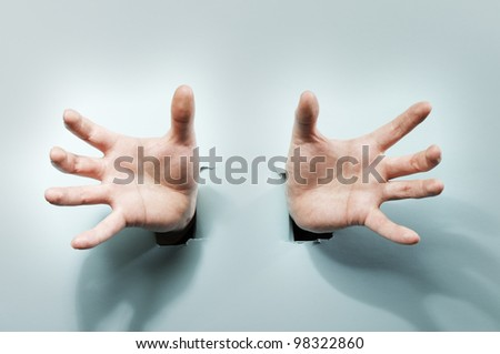 Strange hands coming through holes in a blue cardboard. - stock photo