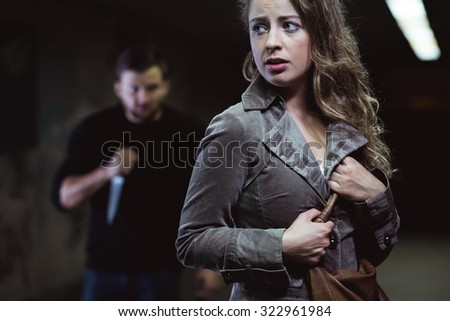 Strange man is planning a murder of young woman - stock photo