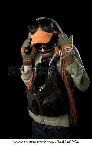 Strange man with paranoid tendencies in goggles, a baseball cap, scarf, gloves and hood on black background.