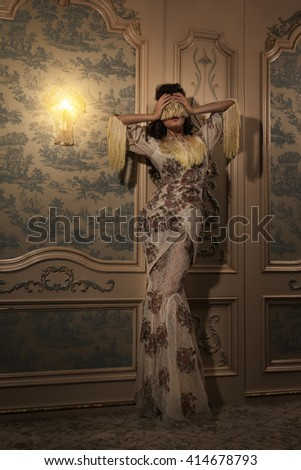 Strange woman in beautiful dress with blindfold on her eyes