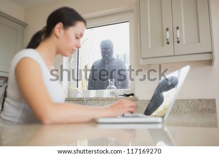 Stranger at the window keeping a wary eye on a sitting woman with a laptop - stock photo
