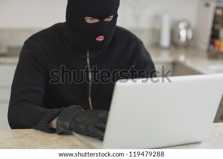 Stranger hacking an unknown laptop and sitting in a kitchen