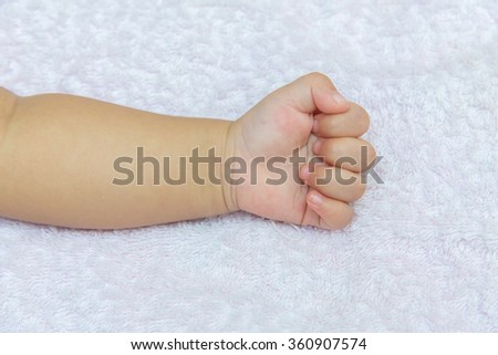 stranglehold Hand of the baby on white diapers. - stock photo