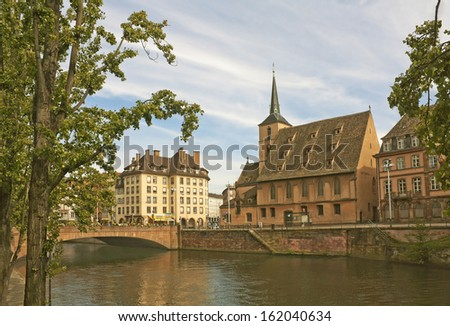 Strasbourg cityscape with old church and river Ill