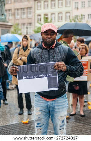 STRASBOURG, FRANCE - APR 26 2015: I am a migrant poster holed by a man at protest against immigration policy and border management which asks for commitment in the wake of migrants boat disasters