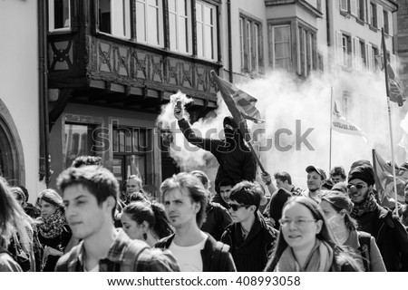 STRASBOURG, FRANCE - APR 20, 2016:Man holding smoke grenade as hundreds of people demonstrate as part of nationwide day of protest against proposed labor reforms by Socialist Government - stock photo