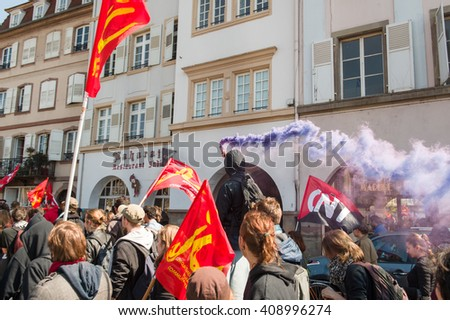 STRASBOURG, FRANCE - APR 20, 2016: Man holding smoke grenade as hundreds of people demonstrate as part of nationwide day of protest against proposed labor reforms by Socialist Government