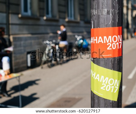 STRASBOURG, FRANCE - APR 8, 2017: Political agitation at French market for the upcoming French presidential election 2017 - Benoit Hamon 2017 sticker with city in the background