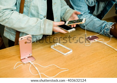 STRASBOURG, FRANCE - APR 9, 2016: Young friends comparing the new Apple SE and iPhone 4 and iPhone 6S phone during the sales launch of the latest Apple Inc. smartphones at the Apple - stock photo