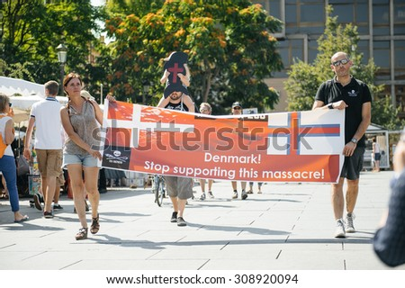 STRASBOURG, FRANCE - AUG 22, 2015: Marine conservation non-profit organization Sea Shepherd protesting against the slaughter of pilot whales and arrest of 7 crew members - placard against Denmark - stock photo