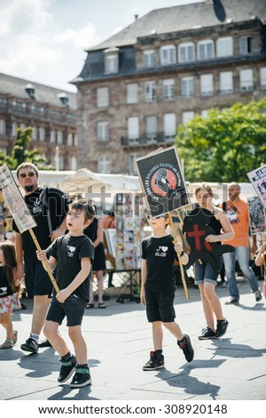 STRASBOURG, FRANCE - AUG 22, 2015: Marine conservation non-profit organization Sea Shepherd protesting against the slaughter of pilot whales and arrest of 7 crew members - kids holding placards - stock photo