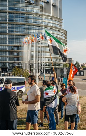 STRASBOURG, FRANCE - AUG 20, 2015: People protesting in front of European Parliament denouncing the Syrian airstrikes on Douma wheremore 80 were killed - waving flag of Syria European Parliament - stock photo