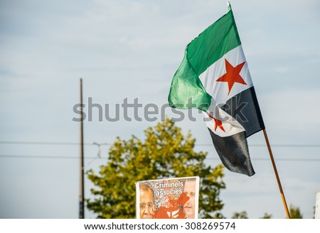 STRASBOURG, FRANCE - AUG 20, 2015: People protesting in front of European Parliament denouncing the Syrian airstrikes on Douma wheremore 80 were killed - Assad and Lavrov killers and Syrian flag - stock photo