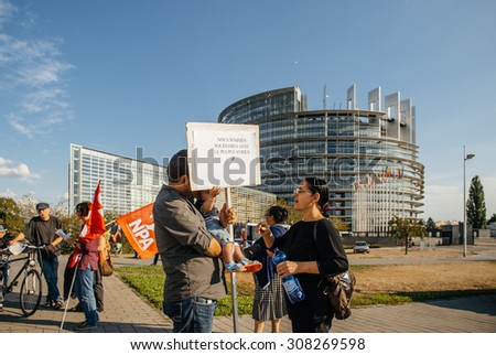 STRASBOURG, FRANCE - AUG 20, 2015: People protesting in front of European Parliament denouncing the Syrian airstrikes on Douma wheremore 80 were killed - we are solidare with Syrian people placard - stock photo