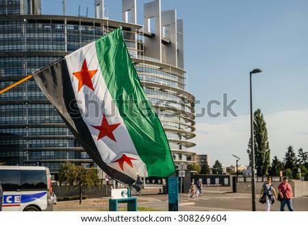STRASBOURG, FRANCE - AUG 20, 2015: People protesting in front of European Parliament denouncing the Syrian wheremore 80 were kille - flag of Syria with Parliament building in the background - stock photo