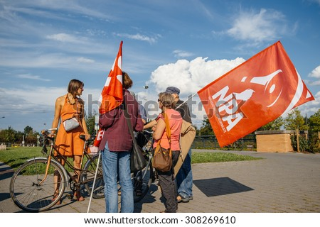 STRASBOURG, FRANCE - AUG 20, 2015: People protesting in front of European Parliament denouncing the Syrian airstrikes on Douma wheremore 80 were killed - people holding new anticapitalist party flag - stock photo