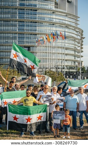 STRASBOURG, FRANCE - AUG 20, 2015: People protesting in front of European Parliament denouncing the Syrian airstrikes on Douma wheremore 80 were killed - waving Syrian flag and placards - stock photo