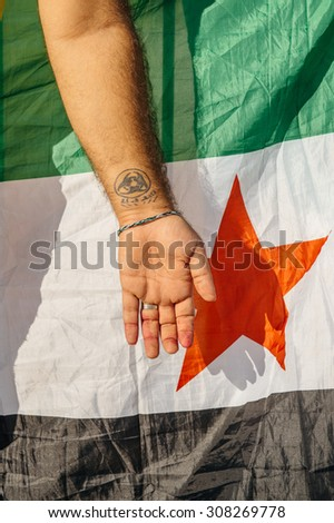 STRASBOURG, FRANCE - AUG 20, 2015: People protesting in front of European Parliament denouncing the Syrian airstrikes on Douma wheremore 80 were killed - syrian war Tattoo on hand and Syrian flag - stock photo