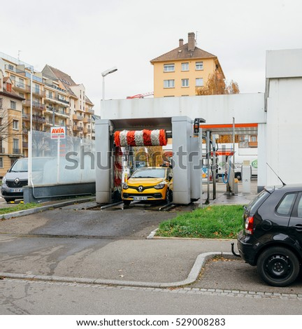 STRASBOURG, FRANCE - DEC 2, 2016: Man attaching antenna to his yellow Renault sport car after using automatic car wash in city
