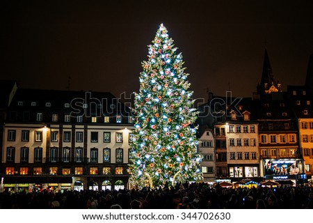 STRASBOURG, FRANCE - DECEMBER 2014: Christmas Tree at the traditional Christmas market in the Place Kleber Strasbourg, Alsace, France with illuminated fair kiosk stores and shining decoration - stock photo