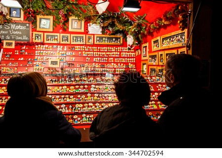 STRASBOURG, FRANCE - DECEMBER 2014: People admiring Traditional Christmas souvenirs at the Christmas market in the historic Strasbourg, Alsace, France  - stock photo